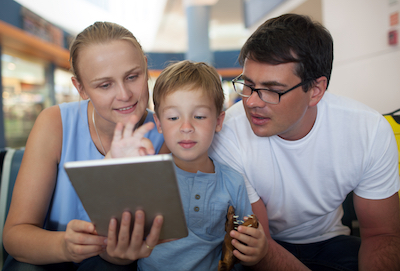 Family looking at scrapbook page on tablet